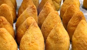 Balls of rice also called arancini di riso in the italian langua. Ge are the typical specialty of southern Italy. The balls of rice are fried in the boiling oil royalty free stock image