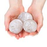 Balls of rock salt in hands. Hands of a woman holding round halite rock salt crystals for alternative medicine royalty free stock images