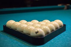 Balls for Russian Billiards are lined with a pyramid at the beginning of the game. white balls on a green table. serious sport, stock photo