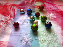 Balls and snowflakes on the Christmas tree. Holiday decorations are scattered on multicolored tulle Royalty Free Stock Photo