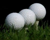 Balls on the tee. Detail of three golf balls Stock Photos