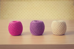 Balls of threads on a wooden table over vintage wallpaper Stock Photos