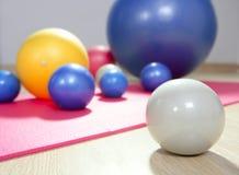 Balls toning pilates sport gym yoga mat. Balls stability and toning pilates sport gym on red yoga mat royalty free stock photography