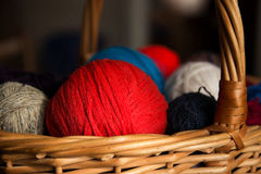 Red ball of wool in basket. Balls of wool of different colors in a wicker basket Stock Images