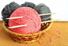 Balls of wool and knitting needles. In a wicker basket Stock Images