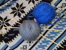 Balls of wool and knitting needles on the knitted sweater Royalty Free Stock Photography