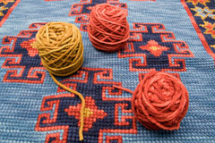 Balls of wool over knitting. Homemade carpet Royalty Free Stock Photos
