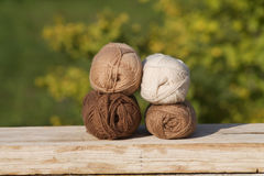 Balls of wool in shades of natural tones on old wood. Green background Royalty Free Stock Images