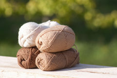 Balls of wool in shades of natural tones on old wood Royalty Free Stock Image