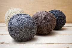 Balls of wool on wooden table Stock Photos