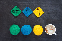 Balls of yarn, crocheted motives and coffee Stock Images