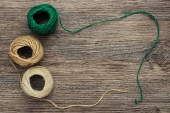 Balls of yarn in green and beige color on a wooden surface. Linen thread in a tangle. The view from the top Stock Images
