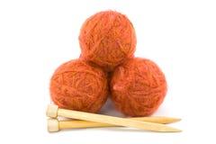 Balls of Yarn with Knitting Needles. Three Balls of Orange Yarn with Wooden Knitting Needles Stock Image