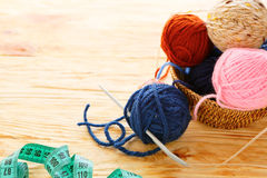 Balls of yarn and knitting needles on board Royalty Free Stock Photo