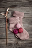 Balls of yarn purple color with a pair of knitted socks Royalty Free Stock Photography