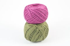 Balls of yarn. Two green and purple balls of yarn on white Royalty Free Stock Image