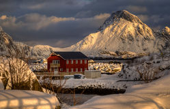 Ballstad rorbu. Red rorbu near Ballstad among snowy mountains at sunset, Lofoten Stock Image