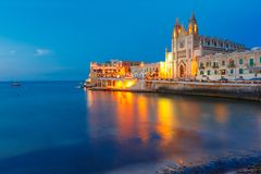 Church of Our Lady at night, Saint Julien, Malta. Balluta Bay and Neo-Gothic Church of Our Lady of Mount Carmel, Balluta parish church, during evening blue hour Stock Photos