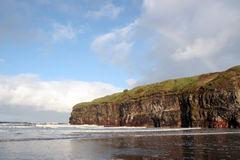Ballybunion beach winter rainbow. A view of the beach cliffs in ballybunion co kerry ireland with rainbow Stock Image