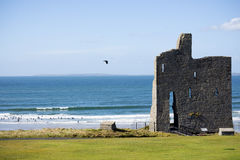 Ballybunion castle ruins with surf school. Ballybunion castle ruins on the wild atlantic way in county kerry ireland as seen from the land Stock Image