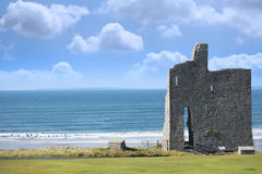 Ballybunion castle ruins with surfers. Ballybunion castle ruins on the wild atlantic way in county kerry ireland as seen from the land Stock Photos