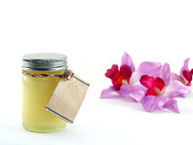 Yellow balm in transparent glass bottle with blank brown paper label and artificial orchid flowers on white background Stock Photo