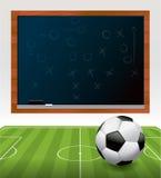 Balón de fútbol en campo con el ejemplo de la pizarra Imagen de archivo libre de regalías