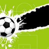 Balón de fútbol en el papel rasgado Imagen de archivo libre de regalías