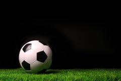 Balón de fútbol en hierba contra negro Fotos de archivo