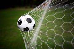 Balón de fútbol en meta Imagenes de archivo