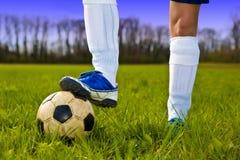 Balón de fútbol y pies del jugador Fotografía de archivo libre de regalías