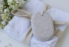 Balneario con la piedra de piedra pómez del cuidado del cuerpo en las toallas blancas, balneario de la belleza del baño Imagen de archivo
