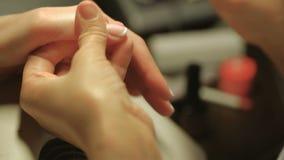 Balneario de la manicura y de las manos Mujer en un salón del clavo de la belleza que recibe una manicura de un cosmetólogo almacen de metraje de vídeo