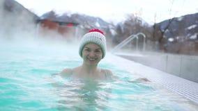 Balneario geotérmico Mujer que se relaja en piscina de las aguas termales La muchacha consigue placer en la piscina termal calien almacen de metraje de vídeo