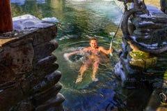 Balneology - badning i gjutjärnvats med mineralvattencontai royaltyfri bild