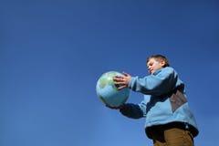 Balão da terra arrendada do menino no formulário do globo Imagens de Stock