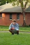 Balompié de la explotación agrícola el ponerse en cuclillas del muchacho Foto de archivo libre de regalías