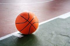 Baloncesto anaranjado en la corte marrón verde del piso del deporte del gimnasio Foto de archivo libre de regalías