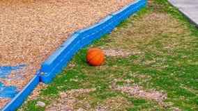 Baloncesto anaranjado que descansa sobre la tierra en un parque en el sol de oro de la hora imagen de archivo libre de regalías