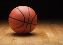 Baloncesto con el fondo oscuro en el piso de madera del gimnasio Fotos de archivo libres de regalías