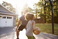 Baloncesto de And Son Playing del padre en la calzada en casa fotografía de archivo libre de regalías