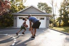 Baloncesto de And Son Playing del padre en la calzada en casa fotos de archivo libres de regalías