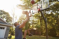 Baloncesto de And Son Playing del padre en la calzada en casa imagen de archivo libre de regalías