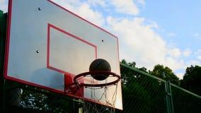 Baloncesto en la calle, entrenamiento que golpea la bola para el baloncesto en la cesta El concepto de deportes, entrenamiento almacen de metraje de vídeo