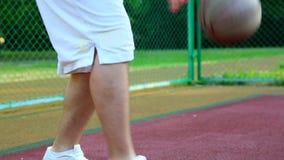 Baloncesto en la calle, entrenando para hacer juegos malabares una bola para el baloncesto El concepto de deportes, entrenamiento almacen de metraje de vídeo