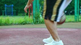 Baloncesto en la calle, entrenando para hacer juegos malabares una bola para el baloncesto El concepto de deportes, entrenamiento metrajes