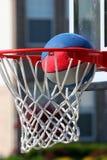 Baloncesto que pasa a través de aro Imagenes de archivo