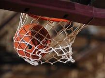 Baloncesto que pasa a través de un aro de baloncesto fotografía de archivo libre de regalías