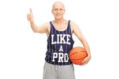 Baloncesto que se sostiene mayor y donante de un pulgar para arriba Fotos de archivo libres de regalías