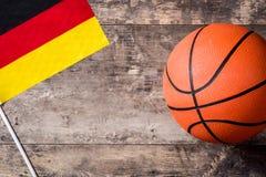 Baloncesto y bandera alemana en la tabla de madera Foto de archivo